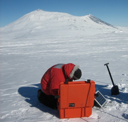 Brian Bonnett deploys a MEVO station with Mt. Erebus in the background